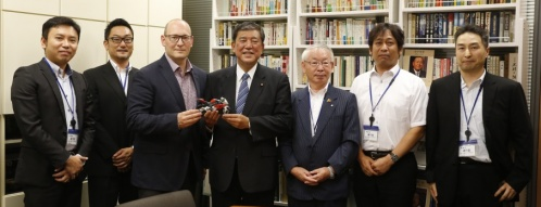 贈られたBMW・S1000RRの模型を手にする石破大臣をリー・ニコルス氏(左隣)と小林町長(右隣)、スタッフらが囲む